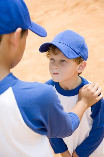 Stock Photo: 4029R-163816 older boy talking down to younger boy at baseball practice