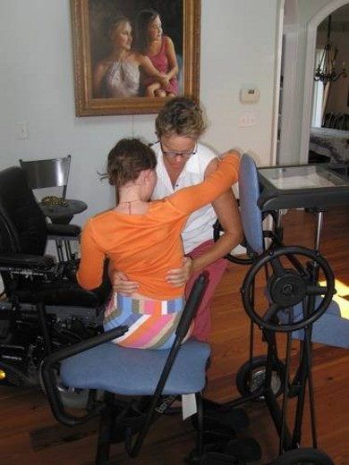 Stock Photo: 4029R-16438 Mother helps daughter transfer from her wheelchair to a ôstanderö for a physical therapy session.