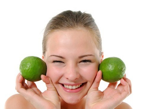 Portrait of a young woman holding two limes besides her two cheek and smiling : Stock Photo