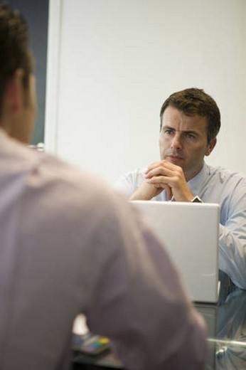 Two men meeting in office, front view, rear view, differential focus : Stock Photo