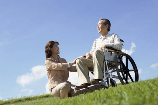 Stock Photo: 4029R-164840 Senior woman crouching by her husband in wheelchair at the park