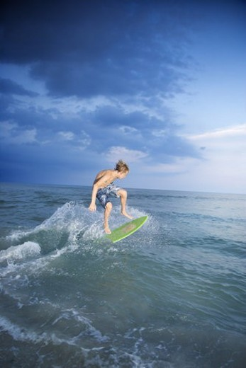 Stock Photo: 4029R-165101 Caucasian male teen riding skimboard.