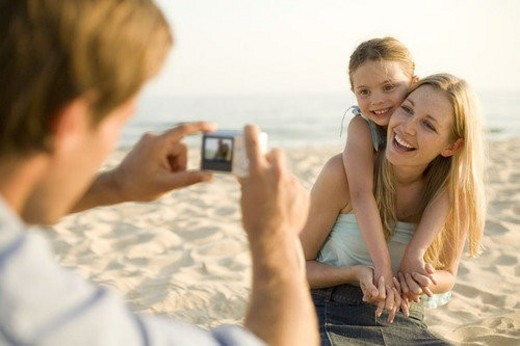 Family on beach, with camera : Stock Photo