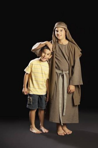 a young boy dressed up as jesus embracing another boy : Stock Photo