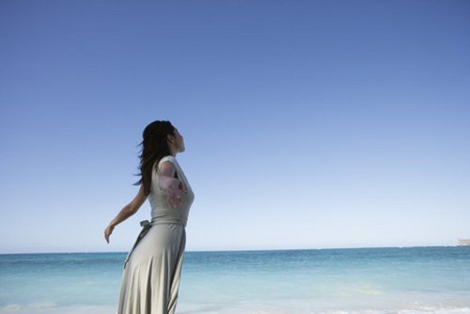 Stock Photo: 4029R-166227 A young woman standing on beach