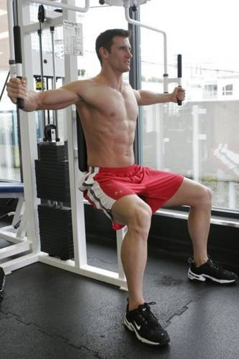 Stock Photo: 4029R-16677 fit male exercising in gym with out a shirt on showing a very ripped muscular body.
