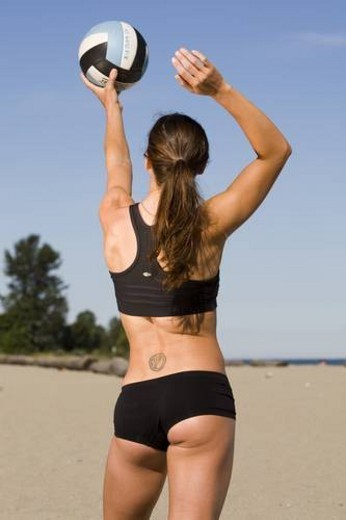 Girl practicing and playing volleyball on the beach at Spanish Banks park in Vancouver, British Columbia. : Stock Photo
