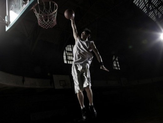 Young man throwing basketball : Stock Photo