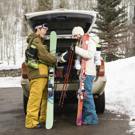 Stock Photo: 4029R-171669 Young couple wearing winter clothes unloading ski equipment from vehicle smiling and laughing.