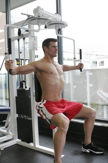 Stock Photo: 4029R-171857 fit male exercising in gym with out a shirt on showing a very ripped muscular body.