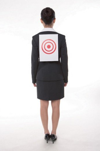 Young woman in business suit, standing, wearing a target on back, rear view, full length : Stock Photo