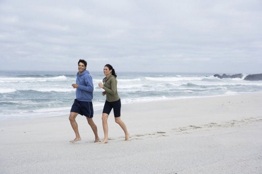 Stock Photo: 4029R-173909 Mid adult couple running on sandy beach, Cape Town, South Africa