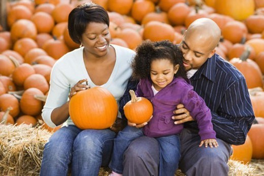 Happy smiling family sitting on hay bales and holding pumpkins at outdoor market. : Stock Photo