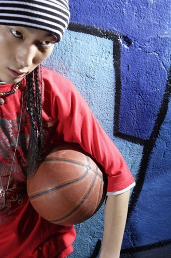 Stock Photo: 4029R-176333 Young man holding basketball in front of graffiti