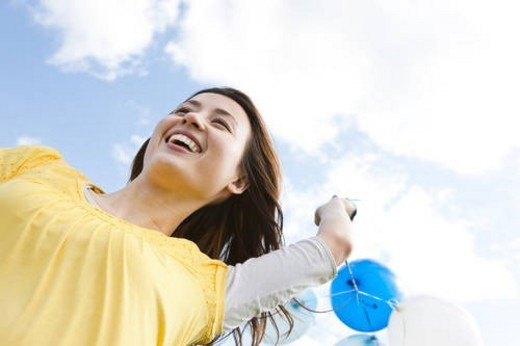 Woman running with balloons : Stock Photo