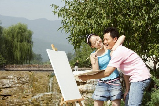 Young woman playing with young man with brush near lake : Stock Photo