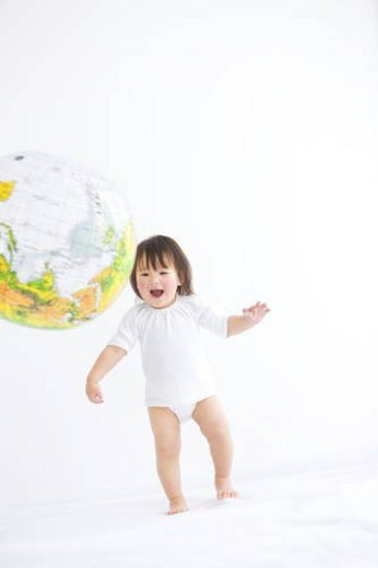 Stock Photo: 4029R-177833 Baby girl playing with globe beach ball