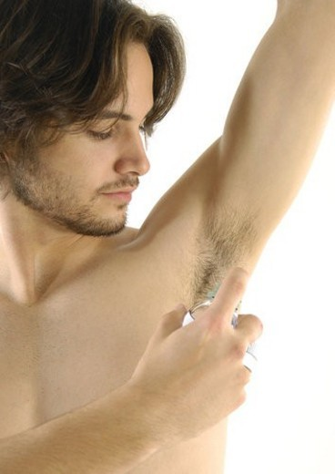 Stock Photo: 4029R-180470 Close-up of a young man applying deoderant to his underarms