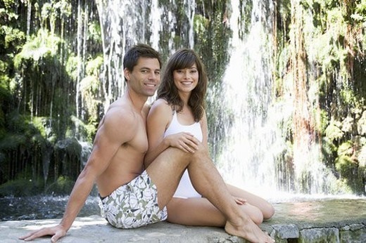 A couple sitting by a waterfall : Stock Photo