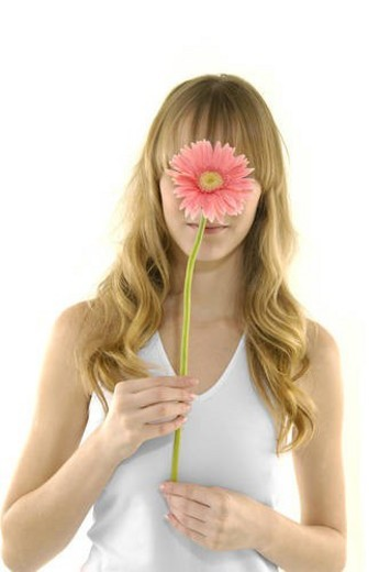 Close-up of a young woman holding a flower in front of her face : Stock Photo