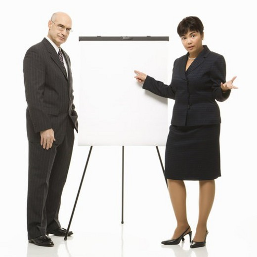 Caucasian middle-aged businessman and Filipino businesswoman standing making presentation against white background. : Stock Photo