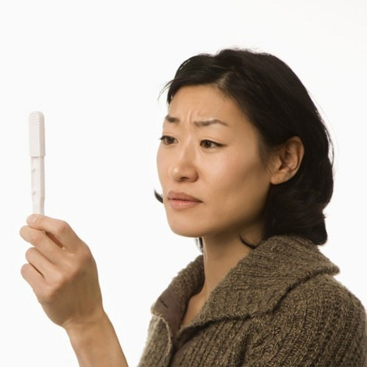 Asian mid adult woman holding up pregnancy test. : Stock Photo