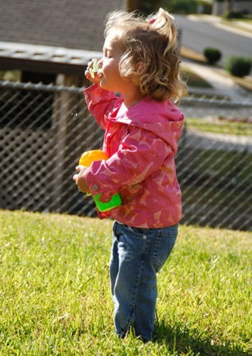 Side profile of a girl blowing bubbles with a bubble wand : Stock Photo