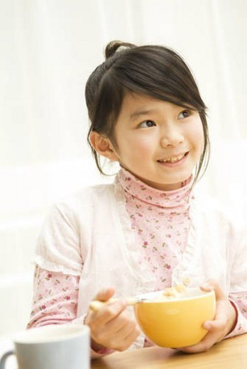 Stock Photo: 4029R-183216 Young girl eating breakfast