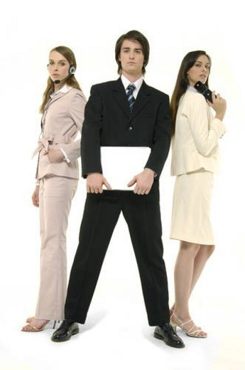 Portrait of a businessman holding a laptop with two businesswomen standing behind him : Stock Photo