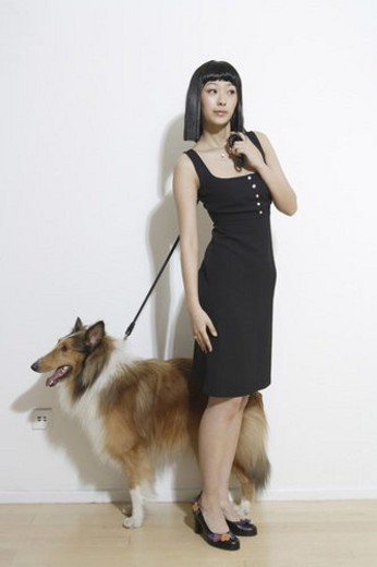 Young woman standing with dog : Stock Photo