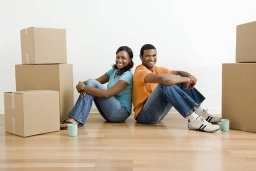 African American male and female couple sitting on floor next to moving boxes. : Stock Photo