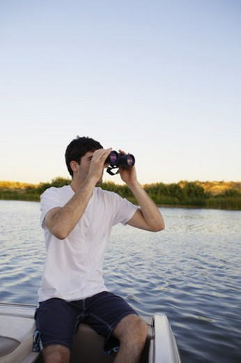 Young man using binoculars at lake : Stock Photo