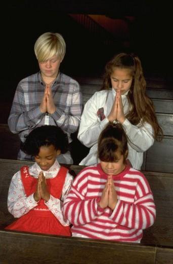 Multi-ethnic youths praying in church : Stock Photo