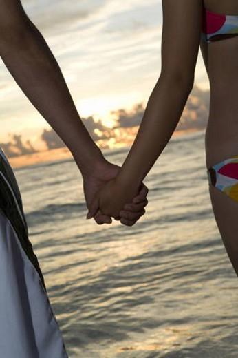 Young couple on beach, hand in hand, Saipan, USA : Stock Photo