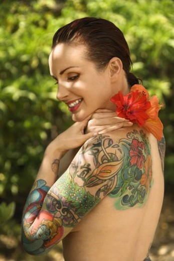 Attractive smiling Caucasian tattooed woman with Hibiscus flower over her shoulder : Stock Photo