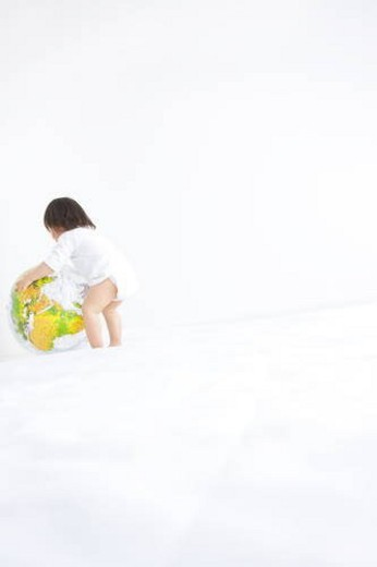 Baby girl playing with globe beach ball : Stock Photo