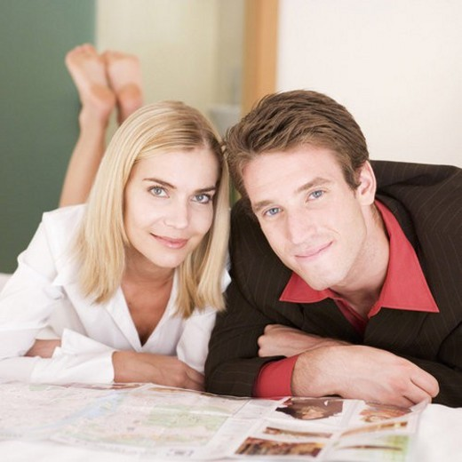 A couple reading a brochure in a hotel bedroom : Stock Photo