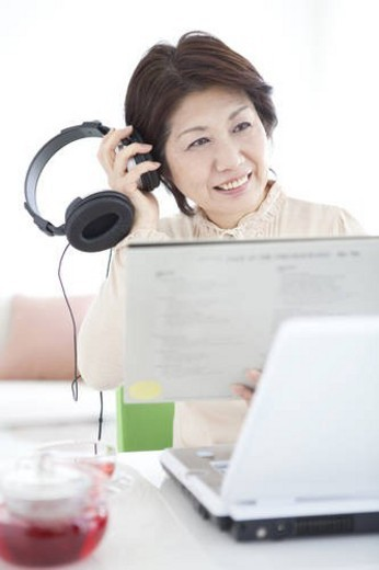 Stock Photo: 4029R-194009 Mature woman listening to music