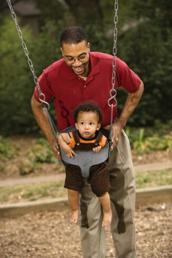 Father pushing young son on swing in park in playground. : Stock Photo