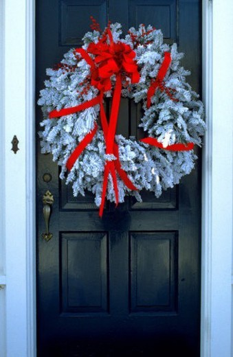 Christmas wreath with red ribbon hanging on front door in Minnesota, USA : Stock Photo