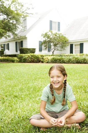little girl with pigtails sitting cross legged on the lawn : Stock Photo