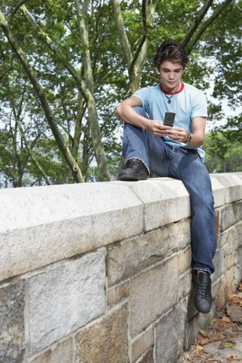 Stock Photo: 4029R-196674 Teenage boy using mobile phone on stone fence