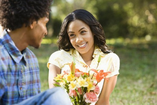 Man giving smiling woman bouquet of flowers. : Stock Photo