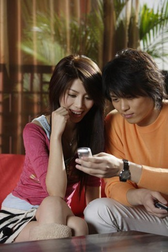 Stock Photo: 4029R-199752 Young couple looking at a moblie phone, smiling