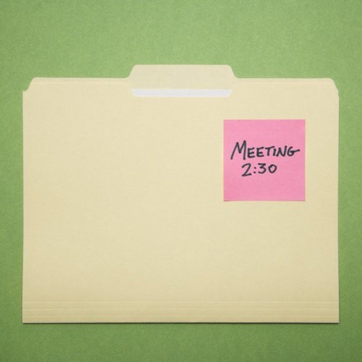 Stock Photo: 4029R-199798 Folder with pink sticky note reminder for a meeting on a green background.