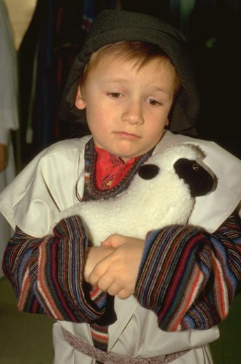 Young shepherd age 7 hugging his lamb at Christmas pageant : Stock Photo