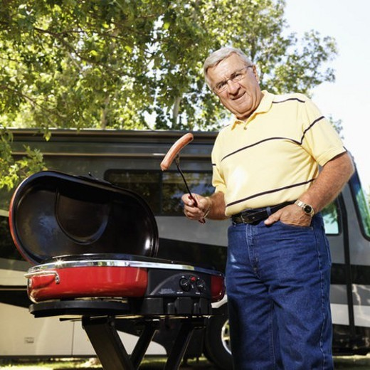 Stock Photo: 4029R-201811 Senior adult man grilling hotdogs with RV in background.