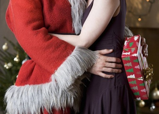 A couple at Christmas with the man wearing a Santa Claus Costume : Stock Photo