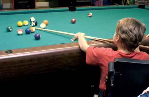 Cute boy, using a wheelchair for mobility, being a sharp shooter at one of his favorite games - pool! : Stock Photo