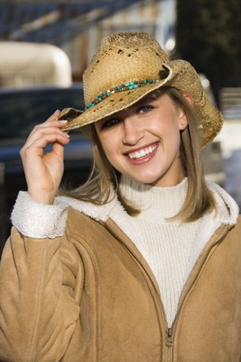 Young Caucasian woman tilting brim of her cowboy hat and smiling at viewer. : Stock Photo